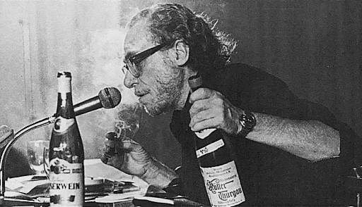 Photo of Charles Bukowski sitting at a desk covered in papers, speaking into a microphone, holding a cigarette in one hand and a bottle of alcohol in the other.