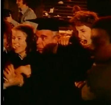 El profesor, ahora con birrete, es conducido por sus alumnos hacia las llamas.